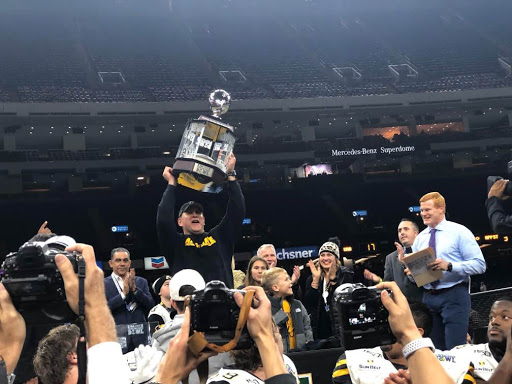 Head Coach Shawn Clark raises the New Orleans Bowl championship trophy